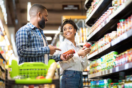 Happy African Family Couple Buying Food In Supermarket, Choosing Products Walking With Cart Along Aisles And Full Shelves Purchasing Groceries Together. Black Spouses Purchasing Essentials Together Archivio Fotografico