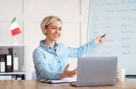 Online foreign languages tutoring. Joyful female teacher giving Italian class, pointing at blackboard with basic grammar rules. Experienced college professor explaining new material to students Stock fotó