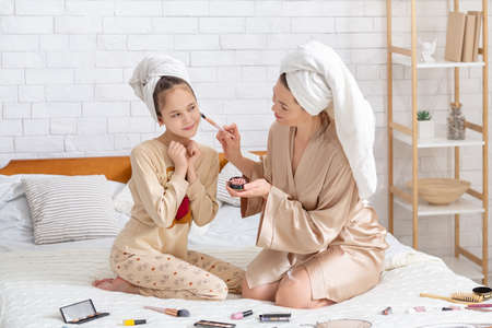 Full length portrait of mom and daughter in comfy homewear and bath towels applying blusher, using makeup on bed at home. Parent and child having spa beauty day with different cosmetic products
