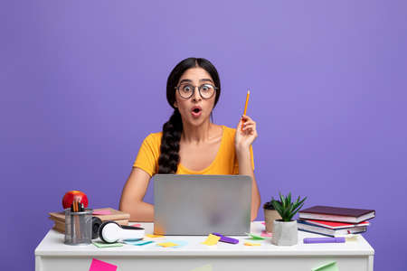 Idea Concept. Excited Young Indian Woman In Eyeglasses Sitting At The Desk Using Laptop And Raising Pencil Up Isolated Over Purple Background In Studio. Amazed Shocked Lady Having Insight, Aha Moment.