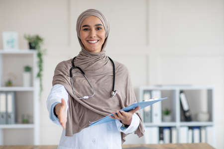 Happy female doctor young woman in hijab with medical folder greeting someone in her office, copy space. Muslim woman therapist holding medical chart and giving hand, clinic interior