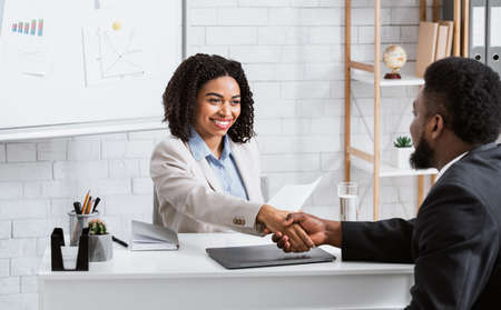 Positive female personnel manager and black job applicant shaking hands before employment interview at company office. Specialist headhunter communicating with vacancy candidate Banque d'images