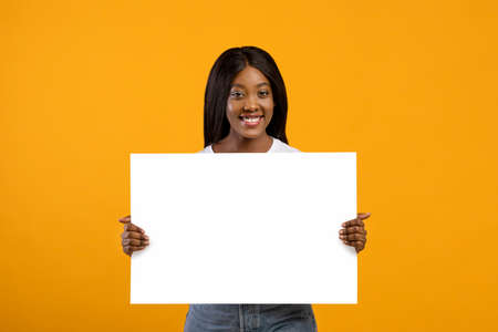 Smiling young black woman holding blank board for advertisement or text on yellow studio background. Pretty african american lady showing empty advertising placard, copy space