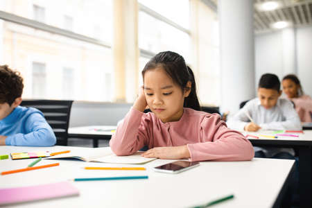 Portrait of focused small asian girl sitting at table in classroom at primary school or kindergarten, reading task in notebook.