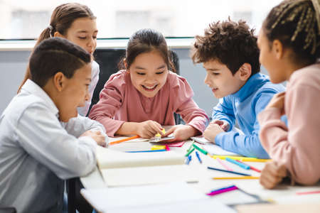 Technology And Pupils Concept. Group of excited multicultural happy junior children sitting at table and using smartphone, playing online mobile games. Modern Device, Gadget Addiction