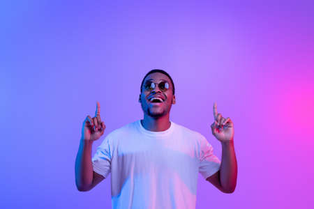 Excited Black Guy Standing Under Neon Light Pointing Fingers Up At Copy Space , Cheerful African American Man In Stylish Sunglasses Demonstrating Free Space Above His Head Over Purple Background Standard-Bild