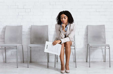 Bored black woman with CV tired of waiting for employment interview at office lobby, free space. Female vacancy candidate applying for job at multinational company. Work search and headhunting concept