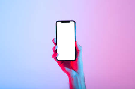 Good app, place for text, advertising, great offer in modern devices. Male millennial hand holds modern smartphone with blank luminous screen, in neon, studio shot, cut out, close up, free space