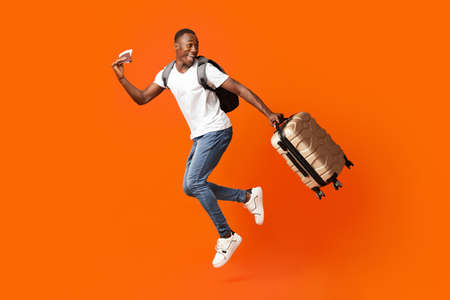 Bye-bye, Im going vacation. Young happy black man with suitcase, backpack, passport and flight tickets jumping up orange studio background. Excited african american guy running and looking back