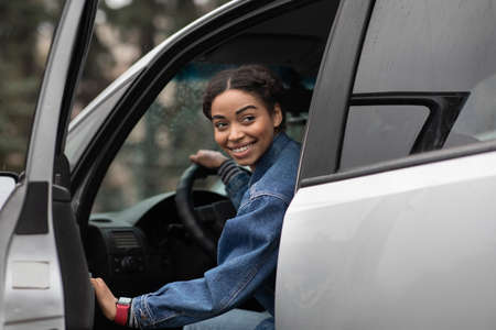 Are you going with me. Friendly smiling millennial african american female driver opens door and looks for fellow traveler, sitting in silver car or lady gets out of auto and looks back, copy space