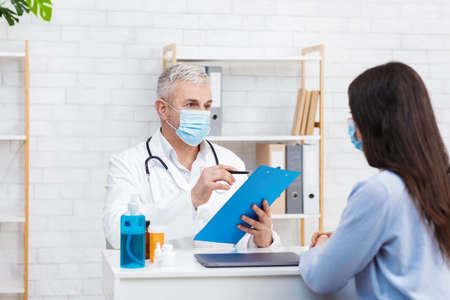 Doctor in white medical uniform and protective mask discuss results or symptoms with female. Adult man GP or physician consult patient give recommendation in hospital at table with jars of pills