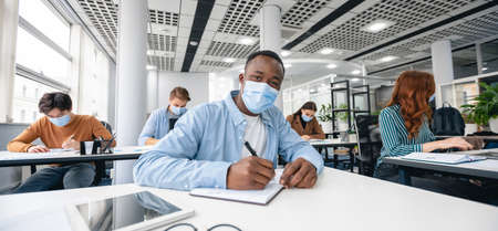 Education Concept. Portrait of black guy wearing disposable surgical mask sitting at desk in classroom at highschool, writing test in notebook, taking notes during lecture, looking at camera, panorama
