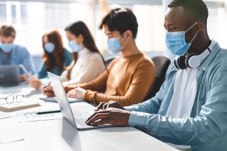 New Normal Reality Rules, People And Workspace Concept. Group of diverse international people wearing disposable surgical masks studying and working sitting at desk, preparing project, using laptop