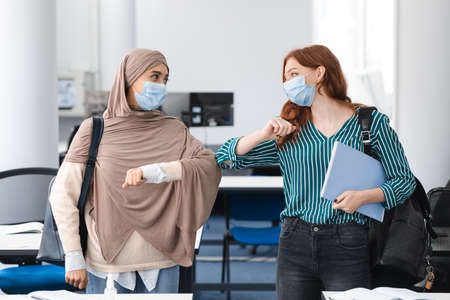 Stop Spreading Virus Concept. Smiling diverse female students wearing protective face masks greeting each other and bumping elbows at classroom. Women standing indoors with backpack and notebooks