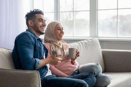 Beautiful muslim couple sitting on sofa at home, drinking tea, looking at copy space. Happy young middle-eastern family wife and husband drinking coffee and watching TV, enjoying time together