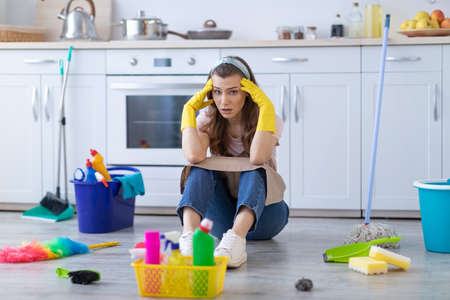 Exhausted housewife or maid sitting on floor at kitchen among cleaning supplies, holding her head in terror. Tired young woman needing rest from household duties