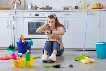 Full length of terrified professional maid sitting on floor at kitchen with cleaning supplies, looking at her watch, being late, missing housework deadline. Sanitary service concept