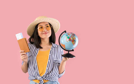 Dream Vacation. Portrait of excited happy asian woman traveller holding passport with plane boarding pass tickets and globe, wearing sunglasses, looking up and dreaming about trip, pink studio wall