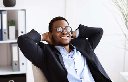 Joyful black businessman in suit reclining on chair and smiling in his modern office, having break after successful working day, achieved goals or had important business meeting, closeup