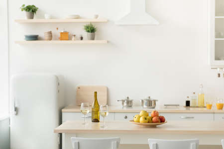 Stylish kitchen interior with green plants, home decoration and rent flat. Plate with apples, glasses and bottle with light wine on table, utensils, orange juice in glasses, white wall, copy space