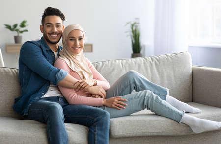 Handsome arab man embracing his pretty wife, spending weekend together, living room interior. Positive muslim couple posing on couch at home, hugging and smiling at camera, copy space
