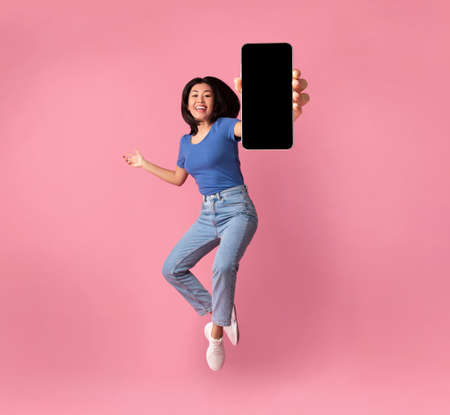 Happy asian young woman showing empty smartphone screen while jumping up over pink studio background, collage, full size photo. Excited lady recommending nice and useful mobile application Banque d'images