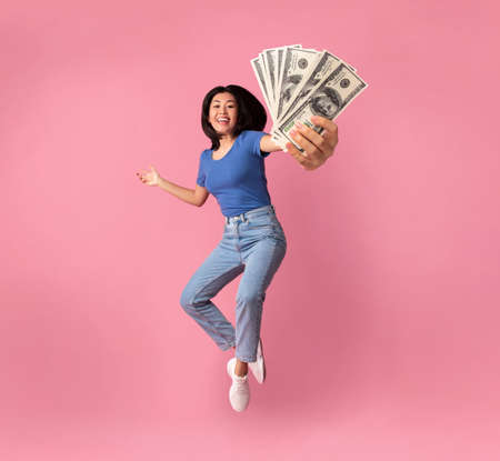 Full length portrait of a joyful young asian woman jumping up high and holding bunch of money banknotes, showing close to camera, celebrating win, isolated over pink studio background, collage Banque d'images