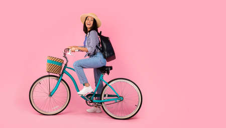 Full length portrait of excited asian woman wearing summer hat and black backpack riding vintage bicycle with wicker basket looking back at free copy space isolated on pink studio background