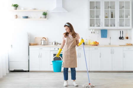 Full length portrait of upset millennial lady with mop and bucket unwilling to wash floor in kitchen, copy space. Millennial housewife sick and tired of cleaning her apartment