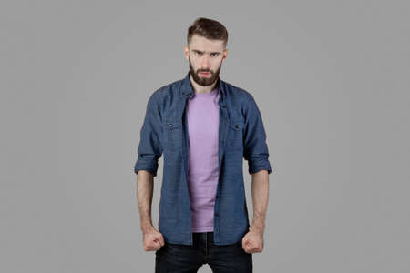 Furious young man clenching his fists, suppressing his anger on grey studio background. Aggressive millennial guy ready for fight or conflict. Human negative emotions concept Stock Photo