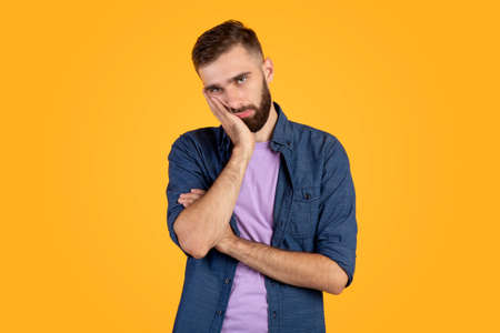 Portrait of bored Caucasian guy leaning on palm and looking at camera on orange studio background. Millennial man being sick and tired of something, annoyed or disappointed, having dull day Foto de archivo