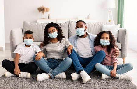 Protection And Healthcare Concept. Portrait of young black family of four people wearing surgical medical face masks during quarantine and self isolation staying at home, sitting on the floor Stock Photo