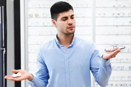 Choice Concept. Portrait of pensive young man looking for alternative to glasses, choosing between eyewear and contact lenses standing in the optical shop, holding case and specs in both hands Stock Photo