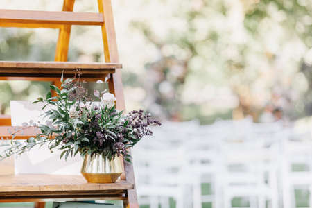 Decorated in boho style. Modern bouquet in vase on wooden shelf for outdoor wedding ceremony on green lawn in summer in sunny day, white chairs for guests blurred background, flat lay, free space