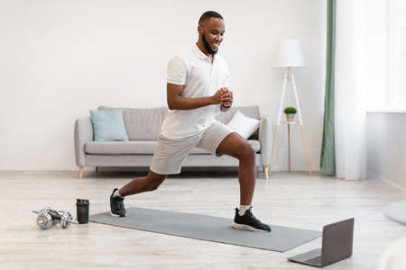 Online Workout. African American Guy Doing Forward Lunge Exercise Watching Fitness Video At Laptop Training At Home. Distant Digital Gym Website, Modern Sporty Lifestyle Concept