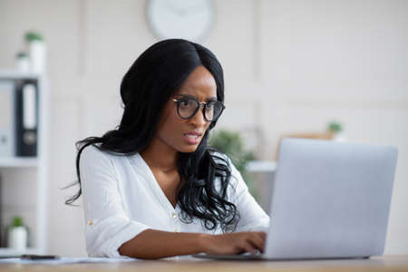 Stressed business lady looking at laptop screen with anger, finding mistake in document, failing to meet deadline at office. Young female entrepreneur not knowing how to correct error in project