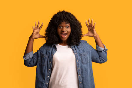 Ecstatic african american young woman yelling with hands up and wide open eyes, yellow studio background. Beautiful black lady expressing strong positive emotions, screaming and gesturing