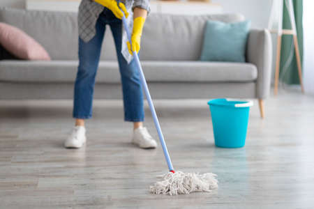 Cropped view of young housewife washing floor with mop at home, closeup of legs. Unrecognizable woman doing domestic chores, cleaning her apartment. Professional house cleanup concept