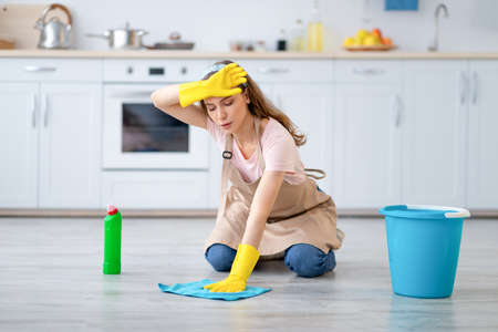 Full length portrait of tired millennial housewife washing floor, wiping her forehead at kitchen. Pretty young woman doing home cleanup, keeping her apartment tidy, feeling overworked Archivio Fotografico