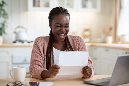 Overjoyed Black Woman Reading Letter In Kitchen And Exclaiming With Excitement, Joyful African American Lady Emotionally Reacting To Good News In Mail, Got Promotion Or University Accceptance