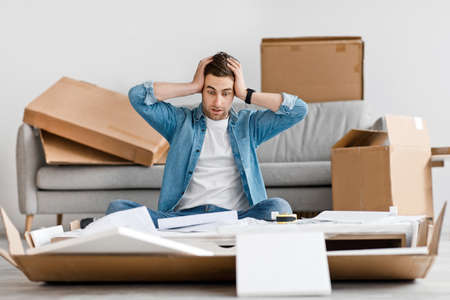 Hard work, task and assembly of new furniture. Upset confused millennial guy holding head, reading instructions, freaking out in interior of living room with table details, tools and boxes, copy space