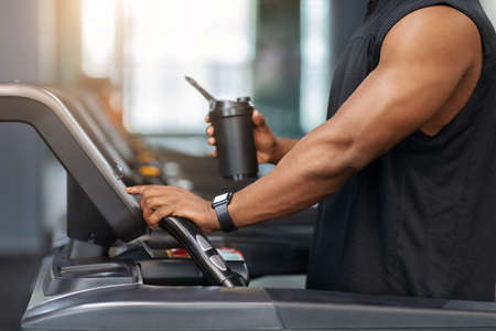 Cropped of muscular african american man holding sports drink, standing on treadmill, drinking protein before running, copy space. Unrecognizable black guy bodybuilder jogging at gym