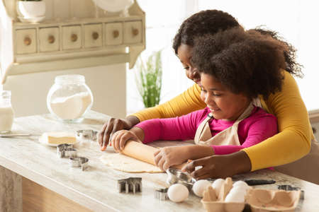 Loving Black Mom Teaching Daughter How To Roll Dough, Having Fun Together In Kitchen At Home, African American Lady Helping To Her Little Child While They Making Homemade Pastry, Free Space
