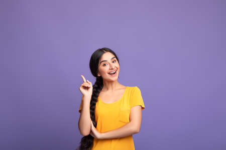 I Have An Idea. Portrait of cheerful young indian woman having great thought, finding inspiration or solution to problem. Positive lady pointing finger up isolated over purple studio wall, copy space Stock Photo