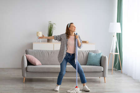 House cleaning with fun. Happy housewife singing her favorite song during cleanup, using mop as microphone, enjoying domestic work. Positive young maid tidying her home with pleasure Banque d'images