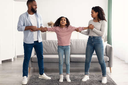 Divorce Concept. Portrait of angry African American parents fighting over their child, mad man and woman quarrelling, pulling daughters hands in different directions. Domestic Violence, Separation