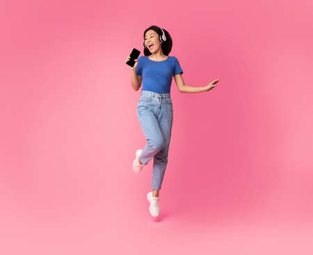Carefree Singer. Asian lady singing favorite song and using cell phone as a mic, dancing and jumping, wearing wireless headphones. Excited woman having fun at pink studio, enjoying sound, full length Standard-Bild