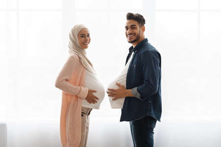 Young pregnant muslim woman and her husband having fun at home, comparing belly sizes. Cheerful arab man with big fake tummy standing next to his expecting wife near window, smiling at camera