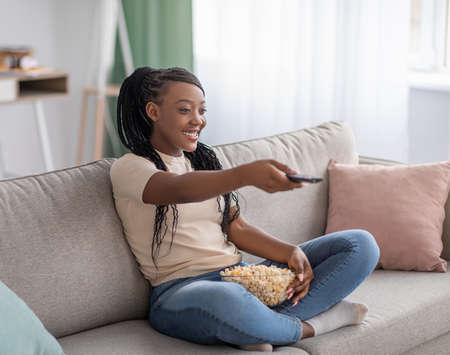 Happy young black woman sitting on couch with TV remote, choosing movie to watch and eating popcorn, copy space. Cheerful african american lady switching channels, home entertainment concept