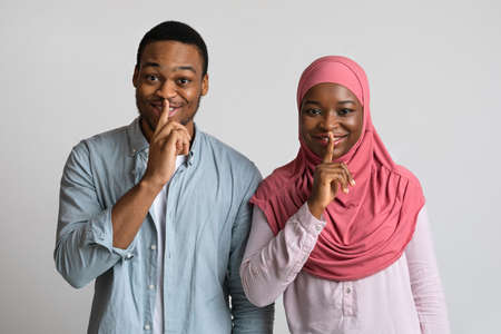 Muslim black couple make silence sign, keep forefingers on lips. Smiling millennial african-american man and woman in hijab holding fingers on lips and looking at camera, grey studio background